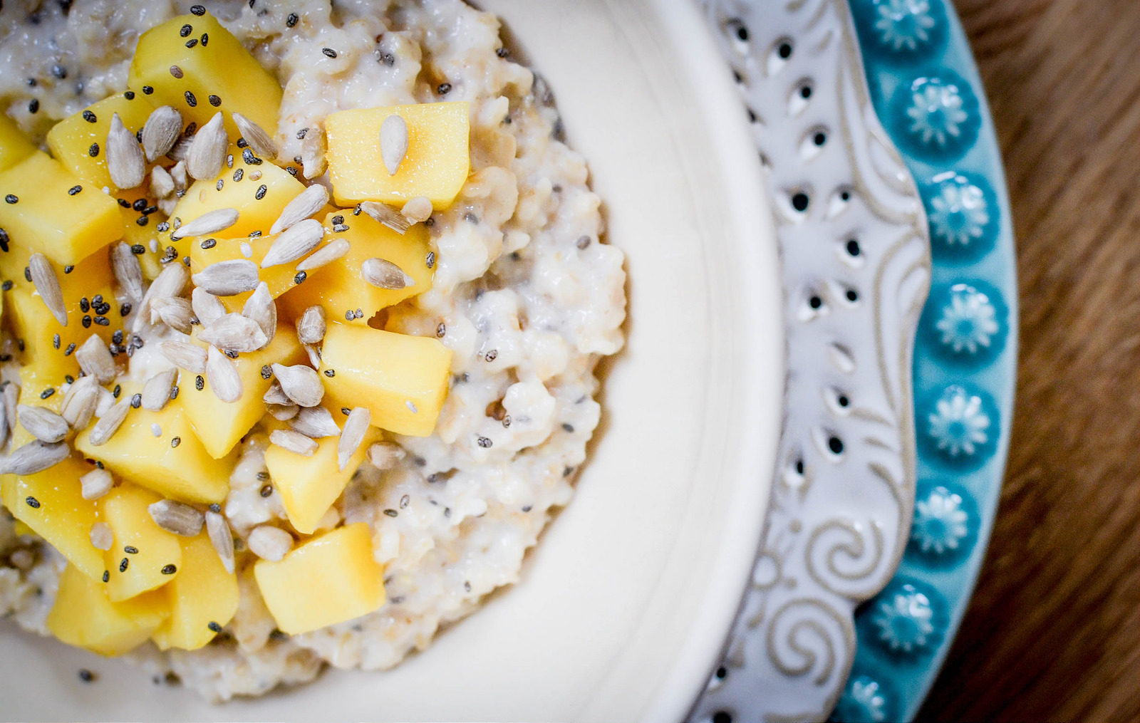 stoats porridge with mangoes, sunflower seeds and a drizzle of orange olive oil